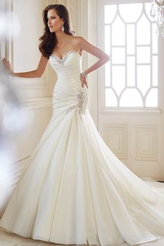 Brides: Sophia Tolli. Couture-inspired chevron pleating is the standout feature of this strapless crystal organza mermaid gown. The sweetheart neckline and side hip are trimmed with matching decedent crystal hand-beaded lace. Ginger also features a back corset partially concealed by matching crystal-beaded lace at the top of the chapel length train. Removable straps are included.