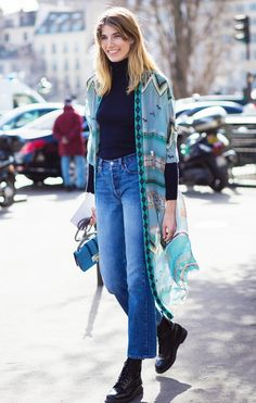 Veronika Heilbrunner wears a turtleneck, sheer printed cape, mini top handle bag, high-waisted jeans, and Dr. Martens boots