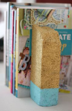 Painted brick bookends. Maybe I can make some of these with the hundred+ bricks we've found amongst the yard