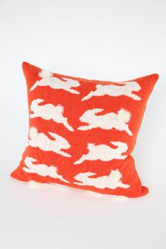Knitted in soft Scottish lambswool 50 x 50 cm, knitted in bright bold orange with white rabbits with a charcoal grey rib on the reverse. On the front and reverse of the cushion are rabbits, the cushion has an envelope opening on the reverse with contrasting rib detail. Every second rabbit on the front of the cushion has a 3-D curly mohair tail. There is a very plump luxurious duck feather pad supplied, made by The Feather Company in Edinburgh Cool hand-wash, gently squeeze out excess wate...