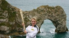 Torchbearer Lisa Devine holds the Olympic Flame at Durdle Door in Dorset during Day 56 of the London 2012 Olympic Torch Relay.