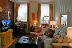 "Love the paint job on the right wall, orange curtains, accent chair, and ""tv stand"" along with neutral couch"
