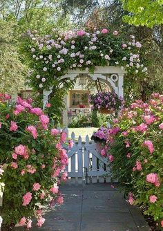 oh how beautiful is this 'old English cottage garden with its' white picket fence and trellis burgeoning with all things pink!