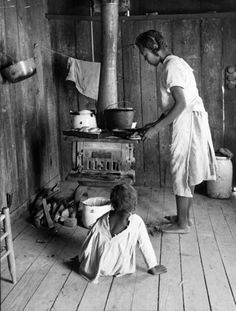 Children of plantation sharecropper Lonnie Fair preparing food on wood stove in sparsely furnished shack.  1936...not to long ago...