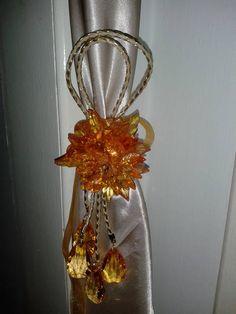 Prendedor de cortina  cristal/acrilico em formato de flor produzido nas cores laranja, marron, ambar, vermelho e cristal transparente. Detalhe em trama de couro e dourado, laço de fitas na cor da sua cortina. Preço unitário. R$ 52,80