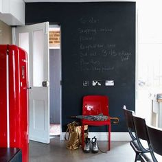 The kitchen wall has been turned into a giant chalkboard by painting the wall in black board paint. A bright red Smeg fridge adds impact in the monochrome setting, and ties in with the red chair.
