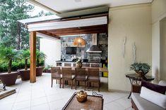 A arquiteta Paula Ferraz criou para o terraço em Alphaville, São Paulo, Brasil, um pergolado de cumaru que recobre parte da área da churrasqueira. A estrutura foi finalizada com uma cobertura de policarbonato, que evita a chuva ou o sol direto.  Fotografia: André Godoy /  Divulgação.  http://estilo.uol.com.br/casa-e-decoracao/album/2016/09/04/pergolados-criam-sombra-e-deixam-o-jardim-e-ate-areas-internas-mais-bonitas.htm?foto=4