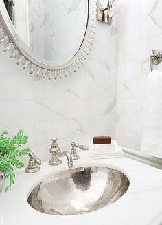calcutta marble tiles backspalsh, glass beaded silver mirror, hammered sink and calcutta marble countertop.