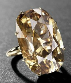 AN IMPRESSIVE COLOURED DIAMOND RING.   Set with a fancy deep brown-yellow cushion-shaped diamond, weighing approximately 35.28 carats, ring size 6, with French assay mark for gold