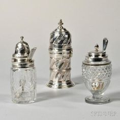 Three Pieces of English Sterling Silver Tableware, two silver-mounted colorless glass condiment jars, each London, with matched spoons (one plate