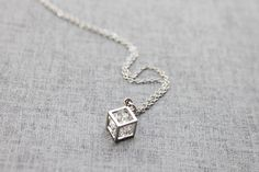 cubic zirconia rattling inside a cube pendant by Ringostone