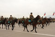 Mounted policemen of the Carabineros de Chile riding through O'Higgins Park in Santiago at the 2012 Chilean Army Day Parade.