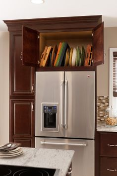 Use a deep cabinet over the fridge to store all of your wider trays and serving platters