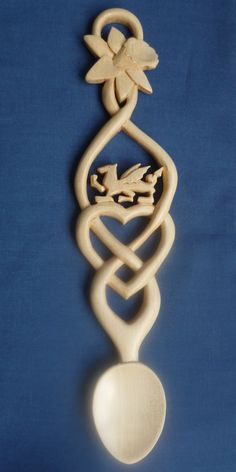 Displays a heart interwoven with a celtic twist knot which represents everlasting love. It also has a daffodil, the national flower of Wales and a Welsh dragon, a symbol of protection. Welsh Dragon, Celtic Dragon, National Flower Of Wales, Welsh Love Spoons, Spoon Craft, Islamic Art Calligraphy, Calligraphy Alphabet, Carved Spoons, Celtic Heart
