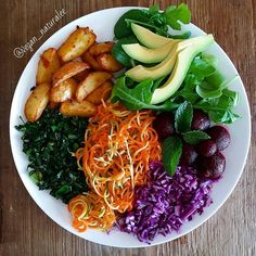 Todays Nourish Plate. Spiralized Carrot and Zucchini lightly sautéed kale with ginger and garlic pickled beets chilli spiced air 'fried' potato's purple cabbage rocket spinach and avocado. All dresssed with a lime apple cider vinigar and olive oil dressing. #vegan #lunch #eattherainbow #foodporn #salad #delicious #happy #healthy #noms #eatclean #forksoverknives #color #nourishbowl by vegan_naturalee