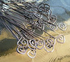 spiral end headpins are hammered for strength and shine and oxidized for a dark antique look. These fiddlehead hea