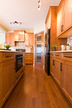 Rustic Alder kitchen cabinets with clean cream quartz countertops and mosaic tile backsplash - Florence Show Home