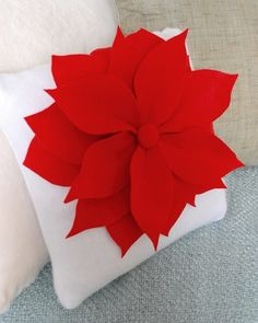 """Simple Sew Poinsettia Pillows: Supplies for a 14 to 18"""" pillow:  pillow insert, 2/3 yard of felt for the pillow form; 1/2 yard of felt for the petals and button; button cover kit or color coordinated button, zipper and thread to match. Step by step instructions."""