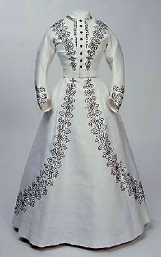 Walking dress, Cox & Ingram, UK, ca. 1865-67. White corded cotton trimmed with black braid in arabesque pattern, with full skirt and long, fitted sleeves. Bodice is machine-sewn, skirt is hand-sewn. Manchester City Galleries