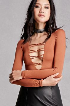 A slub knit crop top featuring a plunging lace-up neckline, long sleeves, and a form-fitting silhouette. This is an independent brand and not a Forever 21 branded item.