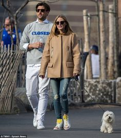 Puppy love: The couple, who married in an intimate ceremony in June 2014, kept it casual and comfortable with Olivia in ripped skinny jeans, trainers and a loose fitting beige coat