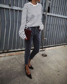 Andy pairs an extra-long sleeved black and white horizontal striped tee with retro style black denim jeans, and simplistic black heels. Tee: Uniqlo, Jeans: Shopbop, Shoes: Acne Studios.