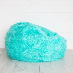 turquoise fur bean bag on wooden floor agains white brick background