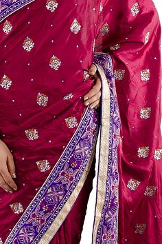 The pleats of the saree have embroidery and stone work. The saree has a purple & golden border which is decorated with thread embroidery, stones and sequins.