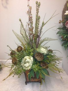 Tuscan arrangement in cream and green with brown seed pods