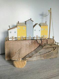 Ce joyeux printemps inspiré de récupération en bois bord de mer port scène dispose de 5 Gîtes ruraux dans la renoncule, galet et blanc, avec des portes en bois et des toits de bois flotté, assis sur un mur de port. Theres un petit auvent en bois, un mât de drapeau haut et port