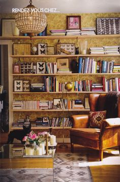 Living room reading nook in the home belonging to architect Laura Gonzalez, wallpaper, open shelving, books, vintage, boho, eclectic, leather chair, southwestern