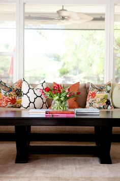 Chic neutral livingroom accented with touches of floral, black and white, turquiose, and orange.  The strong lines of the espresso coffee table anchor the room.