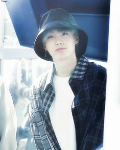 Yoongi is wearing a bucket hat and pulls it off well and i cant even wear a sunhat without looking like cat in the hat