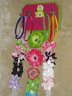 DIY hair bow and headband holder. Ribbon, Wooden Plaque, Paint and Frog from Michaels Craft Stores. Hooks form Lowes Hardware. Bows and Headbands from MOMMY MAID IT on facebook. http://www.facebook.com/mommymaidit