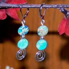 """""""Catamaran"""" earrings by Susen Foster focus on an artistic silverplated swirl with buttons of bright blue Impression Jasper. Simple, gorgeous, and eye-catching, these earrings secure with silverplated leverback clasps"""