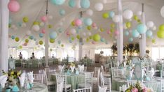 Melody Corporation have suspended a mixture of small and large paper lanterns and spiked tissue paper pom poms in one of their white lined marquees to inject colour and prettiness to this wedding.