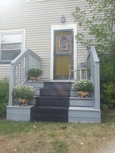 lovely porch- burlap pots + green door + monogram + painted stair 'runner'