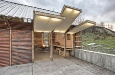 The side facing the deck is composed of individual panels, lined with cotton canvas, which swing up to form an awning.
