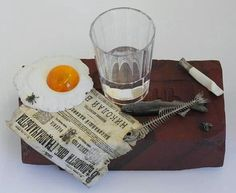 """A unique still life of 1905, which expanded """"gentleman's set"""": eggs, faceted glass unfinished vodka, snacks and smoked cigarettes. Despite its apparent simplicity, still life is made of the most expensive materials jasper, egg white - white stone; egg yolk - amber; newspaper, fish-snack and flies - silver; glass and its contents - crystal; and the butt - crystal and quartz. (Read more about the newspaper)"""