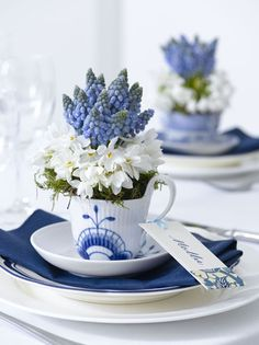 Blue and white place settings and place cards with fresh flowers in teacups