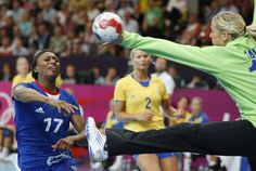 France's Siraba Dembele, left, scores past Sweden's goalkeeper Gabriella Kain, right, during their women's handball preliminary match at the 2012 Summer Olympics, Wednesday, Aug. 1, 2012, in London.
