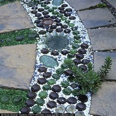 : Patio design with paving slabs interspersed with lines of sliced bottoms from glass or beer bottles & dishes, set in sand topped with green glass or white stone chippings