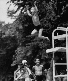 Children at Glen Echo amusement park pool waiting their turn while boy is leaping from diving board into water below.   Photo by Mark Kauffman. 1953