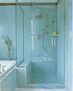 Glass and floor-to-ceiling mosaic tiles in seaglass colors create a beautiful beach style in this bathroom.