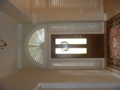 beautiful entryway with framed shutters with a sunburst arch over the front door of this custom Sunnyvale home