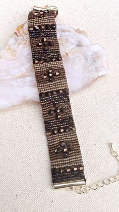 This beaded loomed bracelet is made with delica seed beads in shades of brown and root beer colored fire polished crystals. This earthy beaded