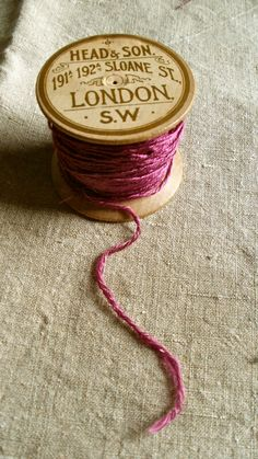 Antique wooden spool with silky crimson thread.