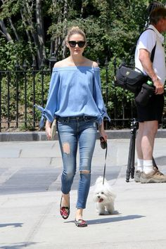 Wheretoget - Olivia Palermo wearing a blue long-sleeved off-the-shoulder blouse, blue ripped skinny jeans, black floral flats, black sunglasses and a white clutch bag