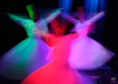 In this Thursday, April 23, 2015 photo, whirling dervish Sayed Abdel Basir, center, a member of the Al-Tannoura Egyptian Heritage Dance Troupe, spins during a performance at the El Sawy cultural center in Cairo, Egypt. The dervishes perform across the city at cultural centers, cruise ships, hotels and weddings. The art form draws its roots from the ecstatic movements of Sufi Muslim mystics seeking a state of delirious oneness with God. (AP Photo/Amr Nabil) Whirling Dervish, Form Drawing, Gautama Buddha, Cairo Egypt, Cruise Ships, Cultural Center, Sufi, Art Forms, Color Combinations