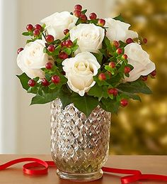 winter white roses are paired with festive red hypericum berries
